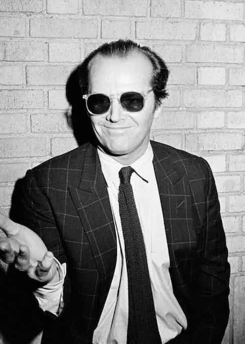 Jack Nicholson wearing his signature sunglasses indoors, circa 1980s.
