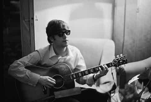 John Lennon of the Beatles plays the guitar in a hotel room in Paris, 1964. Photo by Harry Benson/Express/Hulton Archive/Getty Images.