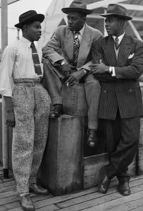 John Hazel, Harold Wilmot and John Richards arrive in Tilbury from Jamaica aboard the 'Empire Windrush', in 1948. Note the wide-legged, Hollywood top trousers on the right, which are cinched tightly with a slim belt. The pinstripe suit on the right is reminiscent of a zoot suit, albeit with less exaggerated proportions.