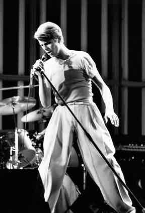 David Bowie displaying his wide trouser prowess, as he caresses the mic, circa 1970s. Note the skinny belt, which accentuates the high-waist and plush swathes of fabric.