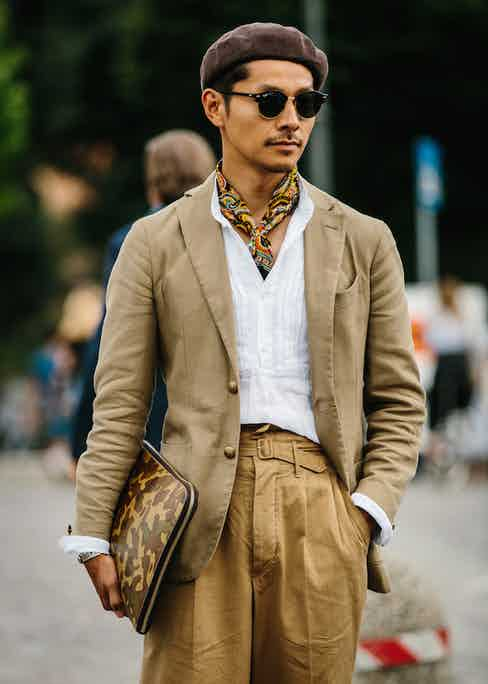 A military-inspired get-up featuring Ghurka-style self-belted, twin-pleated trousers, paisley neckerchief, camouflage portfolio, and jauntily-angled beret. Photo by Jamie Ferguson.