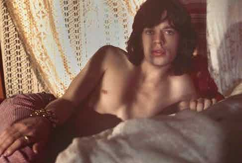 Mick Jagger reclines on a bed in a portrait by Cecil Beaton, 1968, wearing pale pink corduroy flares (and not much else).