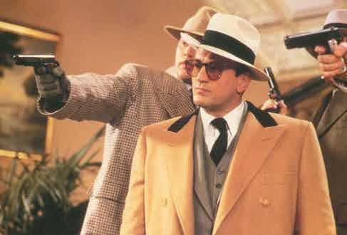 Styled by Armani in The Untouchables, Robert De Niro wears a camel wool-blend overcoat with a contrast collar over a grey three-piece suit, paired with a large felt hat. Photo by Moviestore/REX/Shutterstock.