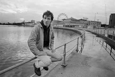 Forever casual in a lightweight jacket, straight leg trousers and a hooded jumper on the boardwalk in Asbury Park, New Jersey, 1979. Photograph by Joel Bernstein.
