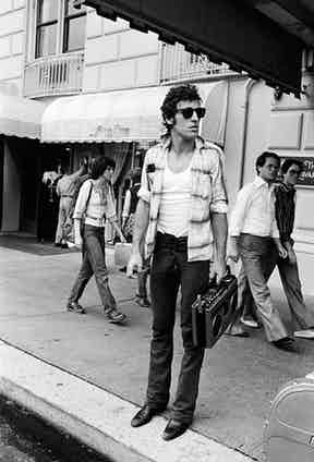 Holding a boombox on a New York sidewalk whilst wearing an open checked shirt on top of a white T-shirt and jeans paired with sunglasses, 1978. Photograph by Lynn Goldsmith.