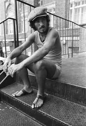 Springsteen looking like the 'New Jersey Che Guevara', wearing a ribbed vest and a baker boy cap while taking a break from the soundcheck at Alex Cooley's Electric Ballroom, 1975. Photograph by Tom Hill/WireImage.