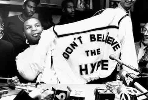 Heavyweight boxing legend Mike Tyson holds up his Don't Believe The Hype jacket at a press conference, 1988.