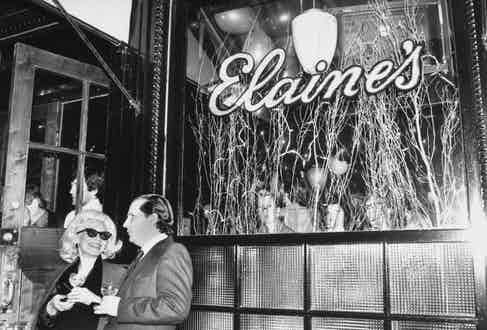 Two guests stand outside the window of Elaine's restaurant in Manhattan, New York. Photo by Robin Platzer/Twin Images/The LIFE Images Collection/Getty Images.