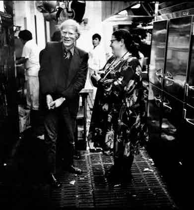 Andy Warhol and Elaine share a joke in the kitchen of Elaine's, circa 1979.