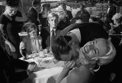 Writer Jared Stern kisses a lady friend as George Plimpton looks on while dining with friends at Elaine's, 1999. Visible in the background is Steve Garbarino, Ivanka Trump and a reflection of the photographer Larry Fink. Photo by Larry Fink/Courtesy Aperture.