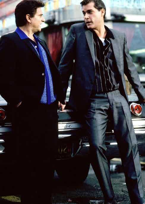 Liotta (right) wears a grey charcoal suit over a button-through knitted polo, alligator skin tassel loafers and a white vest. Joe Pesci wears a similar look, with a dark suit and blue shirt.