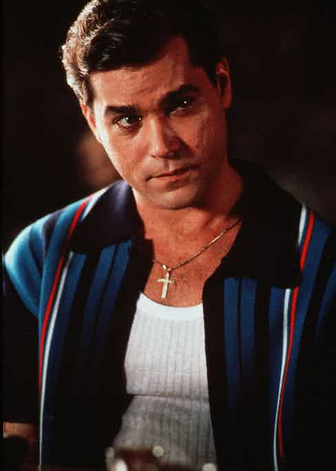 A more casual look for Mr Hill, who wears a knitted contrast-collar striped shirt unbuttoned over a white vest and his gold crucifix. Photo by Warner Bros/Kobal/REX/Shutterstock.