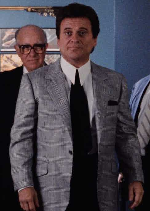 Tommy, played by Joe Pesci, wears a tonal grey unbuttoned glen-check jacket with notch lapels, slanted flap pockets and narrow turn-up cuffs. In his breast pocket, he wears a black pocket square to match his wide, black tie and contrast his crisp white collar and cuffs.