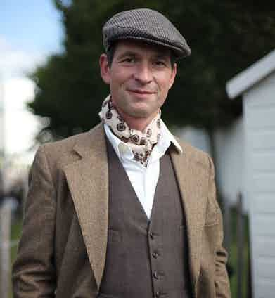 A visitor at Goodwood Revival dresses the part in a textured sports coat, waistcoat and flat cap, 2016.