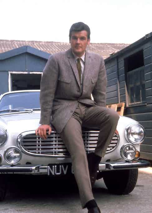 Roger Moore leans against his Volvo car while filming the TV series The Saint at Elstree Studios in North London, 1967. Photo by Pictorial Press Ltd/Alamy Stock Photo.