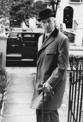 English photographer Cecil Beaton wears a low Derby hat and covert coat with flapped breast pockets, 1955.