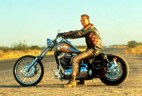 Posing on a Harley Davidson motorcycle in Harley Davidson And The Marlboro Man, 1991. Photo by Moviestore/REX/Shutterstock.