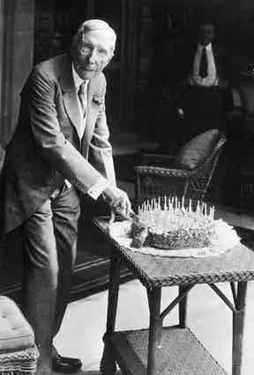 At his home in Pocantico Hills cutting a cake on his 90th birthday, 1929.