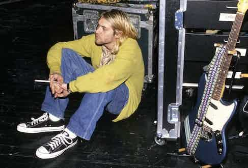 Frontman of Nirvana, Kurt Cobain, sits backstage at a concert in New York wearing his Converse All Stars in 1990.