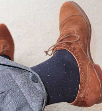An internal button allows the cuff to be fully rolled down on these grey Ambrosi trousers, worn with navy spotted socks and tobacco suede Crockett & Jones Westfield shoes.