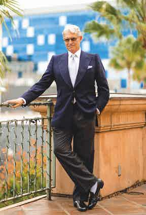 Michael Nouri demonstrates lighter coloured socks with a tonal ensemble of wide-legged charcoal trousers, pale blue ribbed hosiery and black leather slip on shoes.