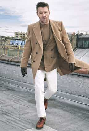 The Rake's cover star Joel Edgerton wears a neutral camel ensemble with white trousers, pale yellow socks and calf leather Balmoral shoes by John Lobb.
