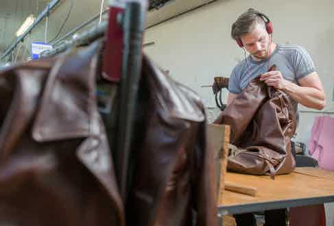 An artisan in Aero Leather's workshop putting the final touches on a jacket.