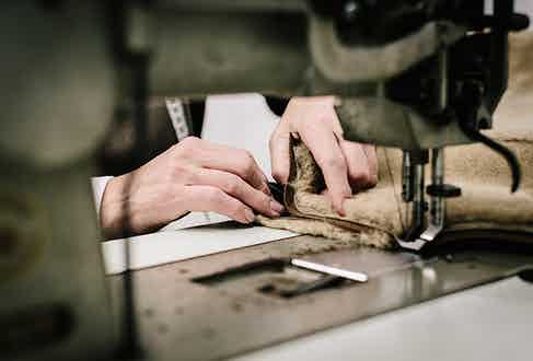 Hand-sewing pieces of shearling together.