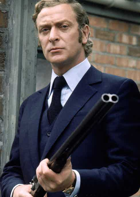 Michael Caine as Jack Carter in Get Carter, 1971. Caine's iconic blue worsted three-piece suit is paired with a stiff-collar light blue shirt and midnight blue tie.