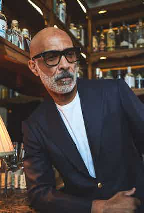 Lono Brazil wears a navy Sciamat blazer with a patch pocket on the chest and pick-stitch detailing over a white Sunspel T-shirt and worn with Oliver Goldsmith glasses.