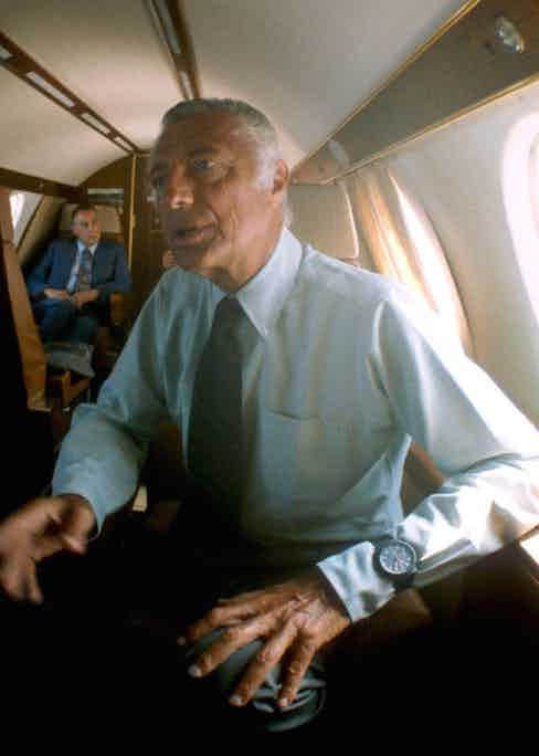 Gianni Agnelli wearing a light blue button-down shirt with his watch worn over the cuff on a private plane in 1975.