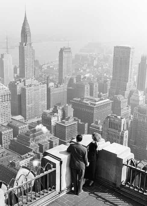 View of a couple sightseeing in New York, looking through  a viewscope down on the city skyline, 1948. The Chrysler building is visible on the left. (Photo by Rae Russel/Getty Images).