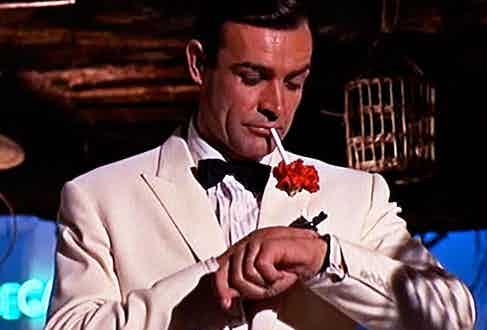 Sean Connery checking the time on his Rolex Submariner ref. 6538, paired with one of the most rakish white dinner jackets in cinema in Goldfinger, 1964.