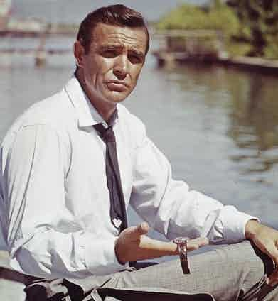 Connery holds out the Submariner with Radium dial on a two-peice leather strap, worn in Dr. No.