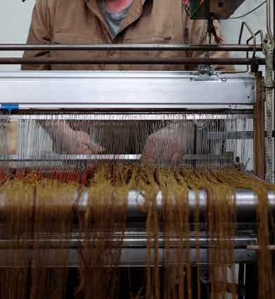 A craftsman tends to one of the looms.