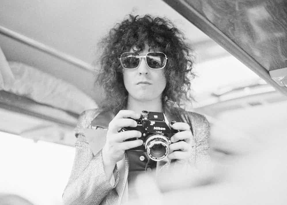 Singer Marc Bolan of English glam rock group T-Rex holds a Nikon camera during a British tour, June 1972. Photograph by Michael Putland/Contributon/Getty Images.