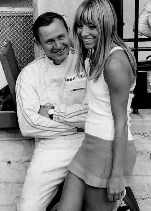 McLaren lounges with an admirer before the 1967 Italian Grand Prix.