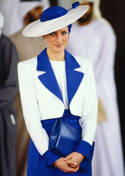 Diana wears a royal blue and ivory ensemble, with a silk turban and Philip Somerville hat in Dubai, 1989.