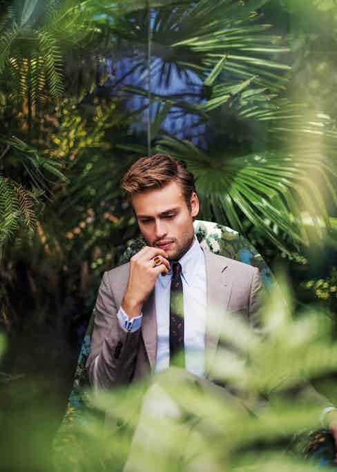 Light grey cotton two-piece suit, Emporio Armani; powder blue cotton shirt and yellow-gold collar pin, both Edward Sexton; black and copper silk feather print tie, The Kooples. Silver-set tiger's eye ring, property of Douglas Booth.