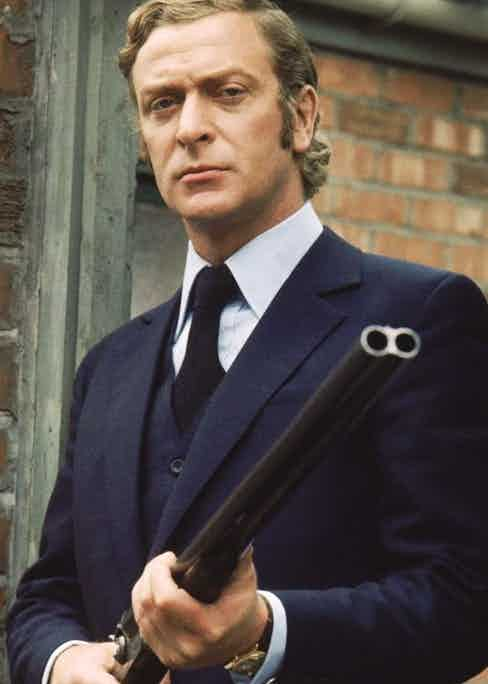 Caine wears a bespoke three-piece suit with slanted pockets, a high notched lapel and a single-breasted waistcoat as Jack in Get Carter, 1971. The accessories of a blue long-sleeved shirt with double cuff, oversized gold and white cufflinks, dark blue silk tie with diagonal rib and Rolex Oyster Day-Date with a brown leather strap all make their contribution to a truly imperious whole.
