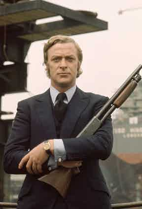 Caine wears a bespoke three-piece suit with slanted pockets, a high notched lapel and a single-breasted waistcoat as Jack in Get Carter, 1971. Paired with a blue long-sleeved shirt with double cuff, oversized gold and white cufflinks, dark blue silk tie with diagonal rib and Rolex Oyster Day-Date with a brown leather strap, this look inspired Chester Barrie's homage to the film (below).