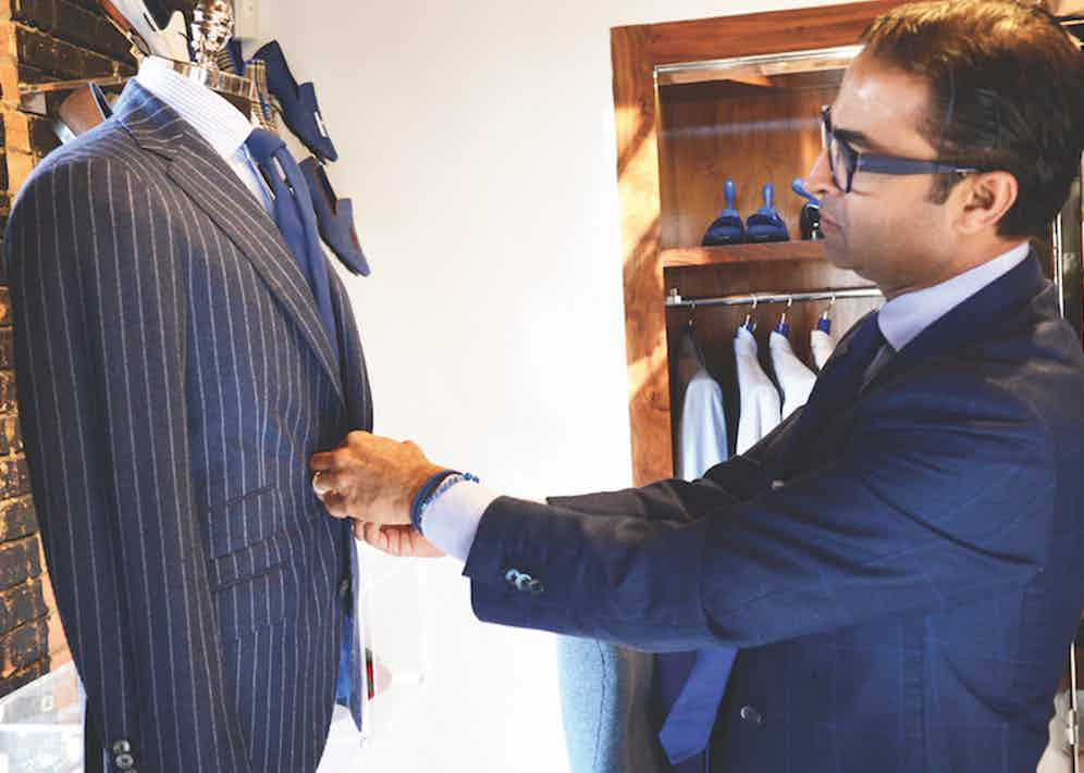 Co-Founder and Creative Director Ed Shaikh inspects his merchandise at his store in Dallas.