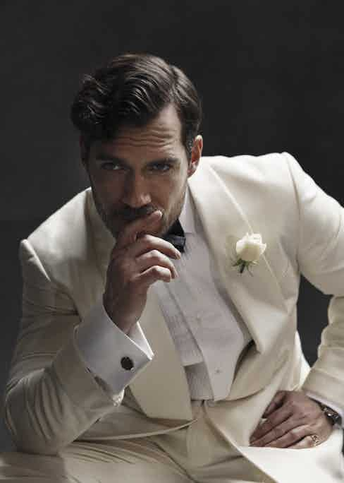 Cream wool Drake shawl dinner jacket, white cotton pleat front shirt and black silk bow tie, all Ralph Lauren Purple Label; ivory virgin wool trousers, Anderson & Sheppard Haberdashery; white-gold Day-Date 40 with olive green dial, Rolex. Yellow-gold signet ring, property of Henry Cavill. Yellow-gold cufflinks, property of The Rake.