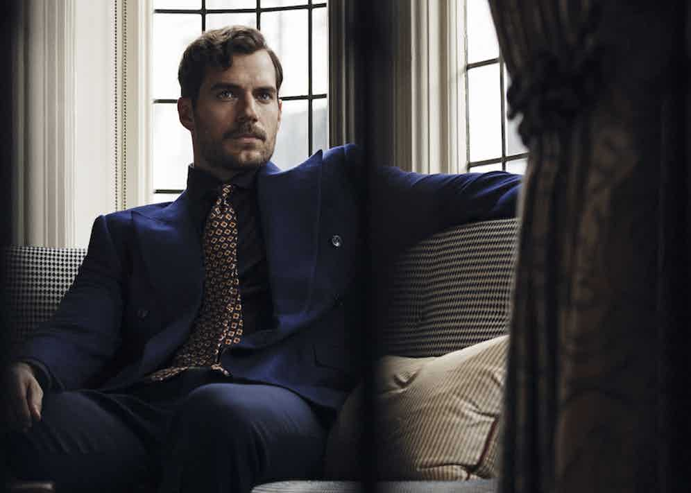 Navy cotton jersey shirt, Pal Zileri at Harvey Nichols; navy cotton drill trousers New & Lingwood. Navy and gold silk printed tie, property of The Rake. Bespoke navy double-breasted wool blazer, Cifonelli, property of Henry Cavill.