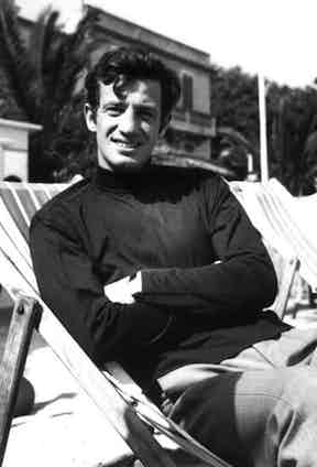 Jean Paul Belmondo's style is simple and clean cut as seen here, wearing a black polo neck and tailored trousers at Cannes Film Festival, 1965.