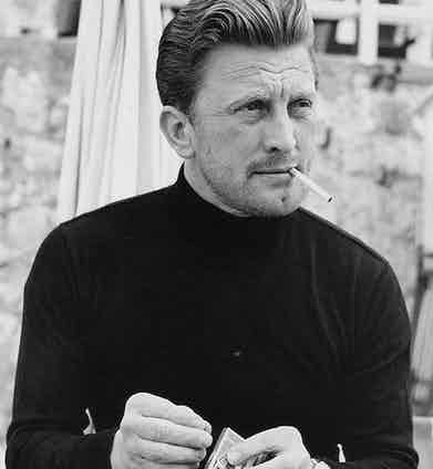 Kirk Douglas' casual ensemble includes a simple black polo neck and perfectly combed hair at Cannes Film Festival, 1953.