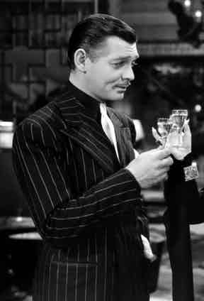 A suave Clark Gable wears a black pinstripe suit and black cotton shirt contrasted with a white silk tie as Harry Van in Idiot's Delight, 1939.