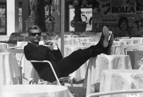 Marcello Mastroianni wears a classic black single-breasted suit, white shirt and retro sunglasses as Guido Anselmi in the film 8½, 1963.