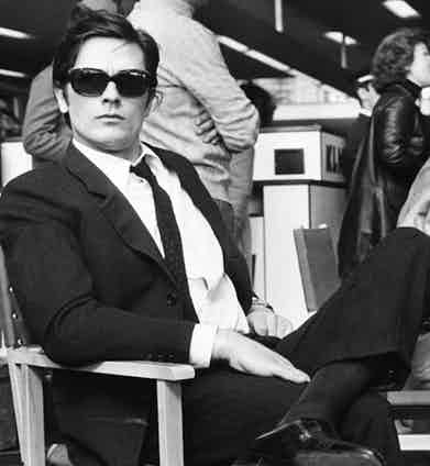 Alain Delon is the epitome of understated sophistication in a black single-breasted suit, woven black tie, white shirt and black-rimmed sunglasses as he reclines in the Piazza della Minerva, Rome while filming Le Clan des Siciliens, 1969.