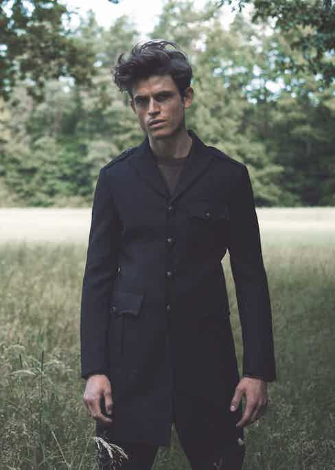 Luc Van Geffen wears black wool and silk military coat, DSquared2; military green wool jumper, Orlebar Brown; indigo blue waxed denim jeans, Ermanno Scervino. Originally published in Issue 47 of The Rake.
